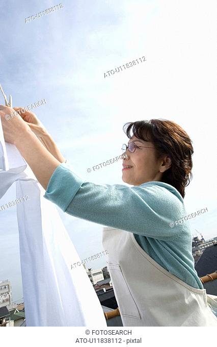 A Senior Adult Woman Hanging Out the Laundry Under the Sky, Side View, Low Angle View