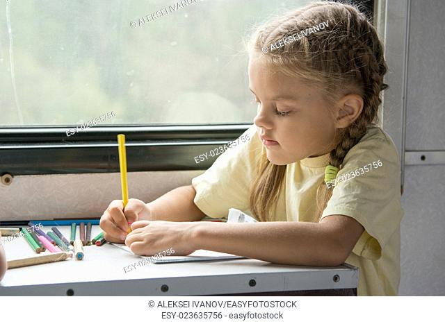 Six year old girl draws a pencil in a notebook for a side table in the second-class train carriage