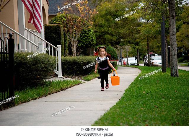 Girl trick or treating in cat costume walking along sidewalk