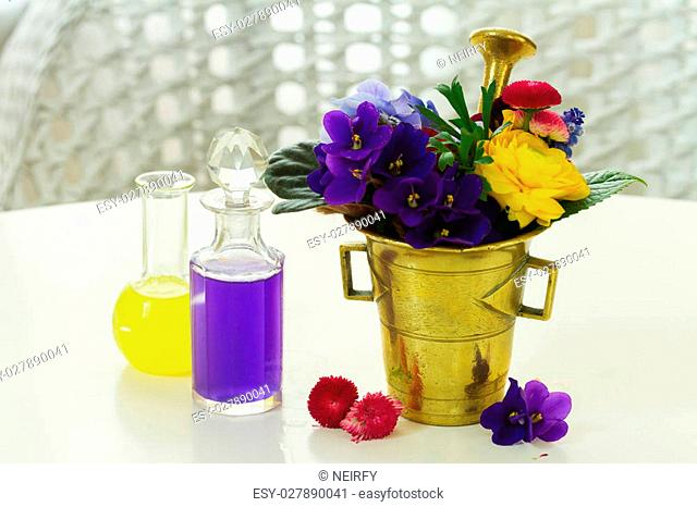Flowers, brass mortar and bottles of potions, herbal medicine