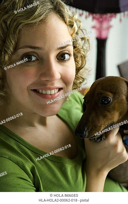 Portrait of a woman holding small dog