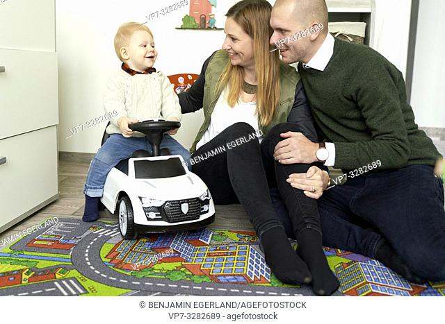 parents with baby toddler child on bobby-car in children's room, little family at home, in Cottbus, Brandenburg, Germany