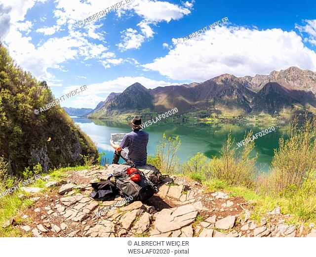 Italy, Lombardy, spring at Lake Idro, hiker sitting with map at observation point