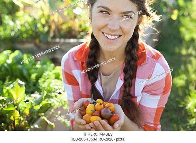 Smiling woman with handful of cherry tomatoes