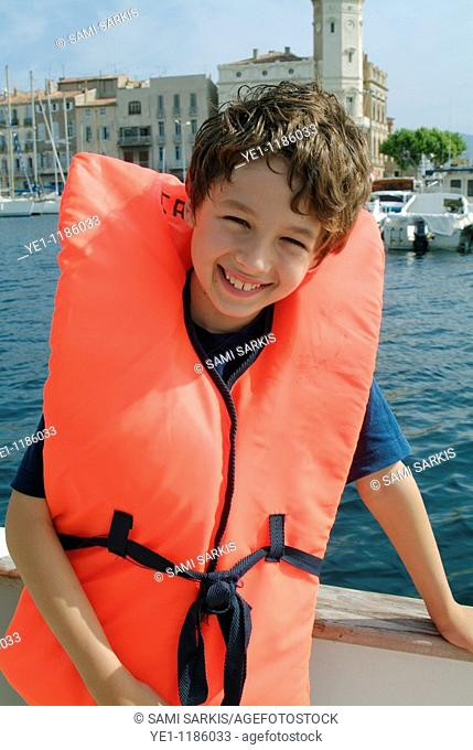 Young boy wearing a life jacket on board a boat, La Ciotat, Provence, France