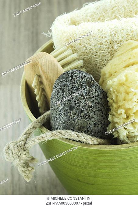 Bowl of bath supplies, brush, pumice stone, sponge and loofah
