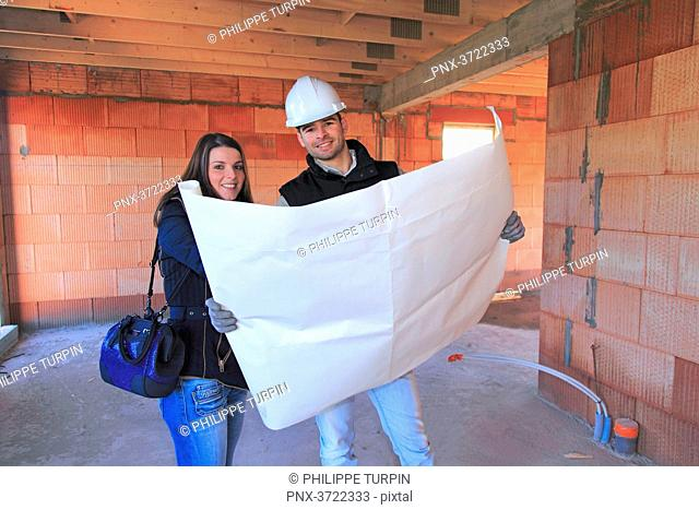 France, young architect and customer in a house in construction