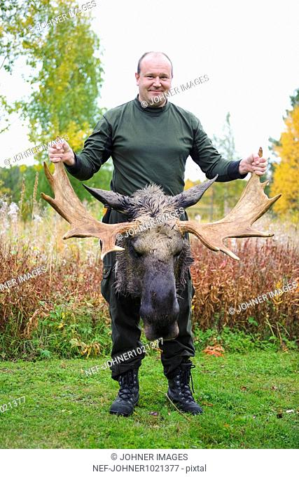 Man holding antler of dead moose