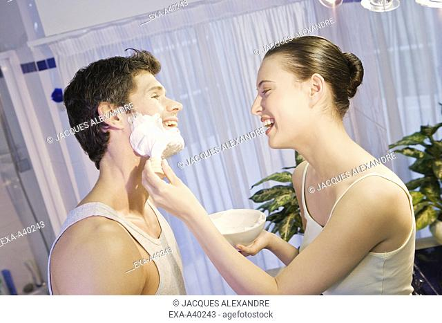 Young woman applying shaving cream to young man