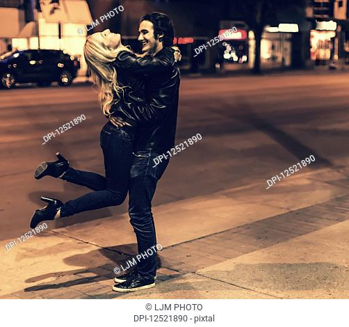 A young couple wearing black leather jackets being playful on a city sidewalk at night; Edmonton, Alberta, Canada