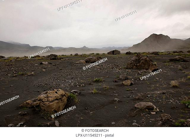 Rugged mountain landscape with dry riverbed and dust rising