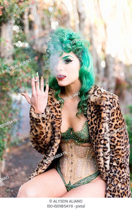 Woman with dyed green hair wearing corset smoking