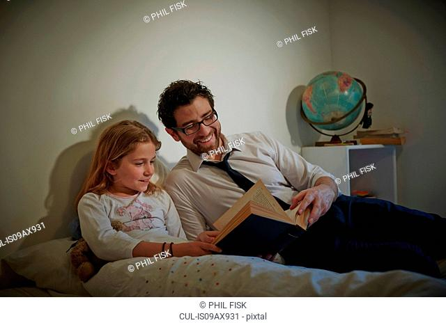 Businessman reading storybook to daughter at bedtime
