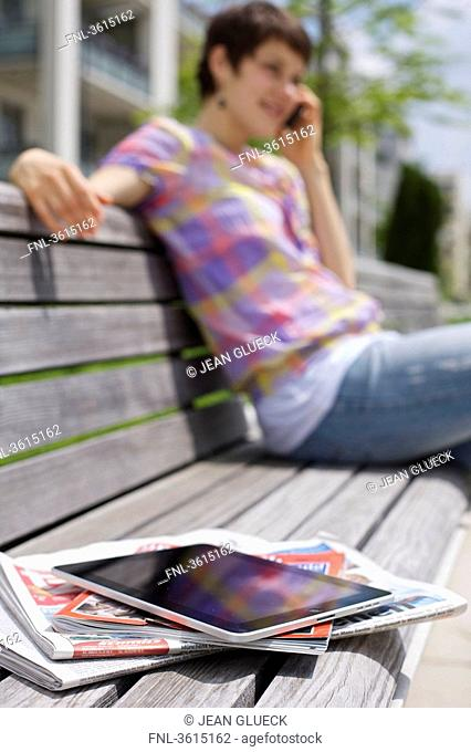 Young woman with cell phone, iPad, newspapers and magazine on a bench