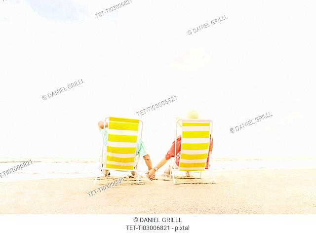 Rear view of couple sitting in lounge chairs on beach
