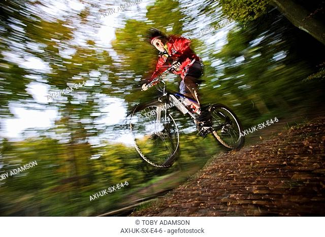 Man mountain biking in woodland, Sussex, England