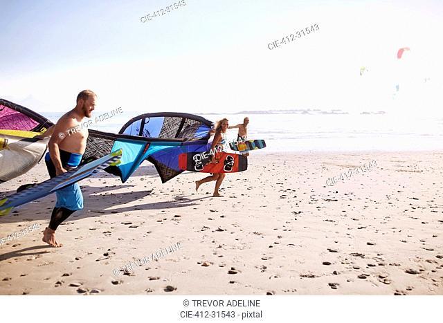 Friends running with kiteboarding kites on sunny beach