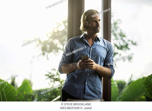 Handsome man holding smartphone in contemporary design house with glass facade surrounded by lush tropical garden