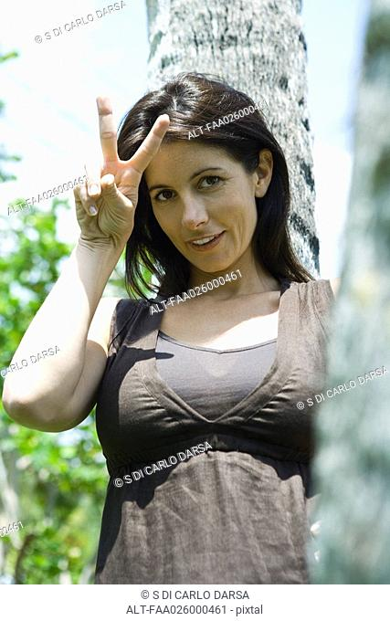 Woman holding up peace sign outdoors, smiling at camera