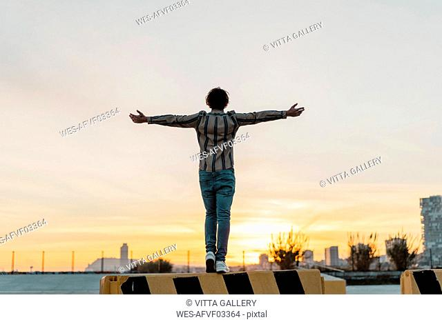 Back view of man with arms outstretched standing on barrier enjoying sunset, Barcelona, Spain