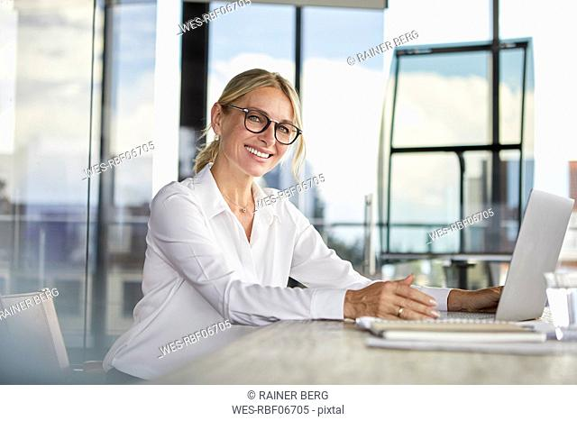 Businesswoman sitting at desk, using laptop, smiling friendly