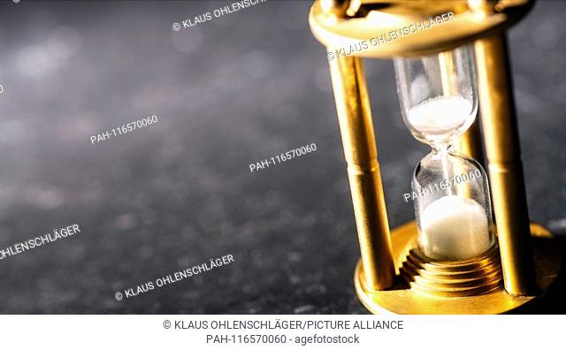 Sand trickles through an hourglass, symbolizing timekeeping. | usage worldwide