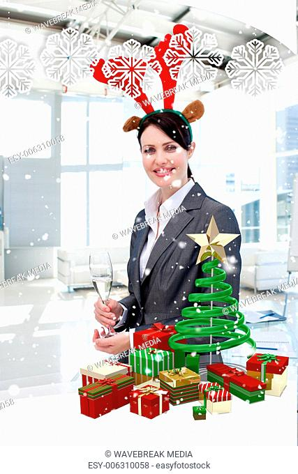 Smiling businesswoman with a novelty christmas hat drinking champagne