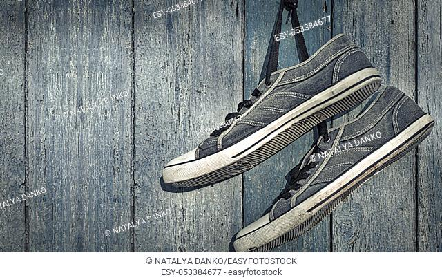 textile torn sneakers hanging from a nail on a background of blue wooden wall, empty space on the right