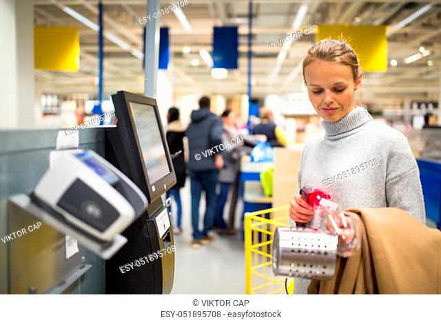 Pretty, young woman choosing the right stuff for her apartment in a modern home furnishings store (color toned image; shallow DOF)