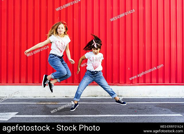 Sisters jumping on street in front of red wall