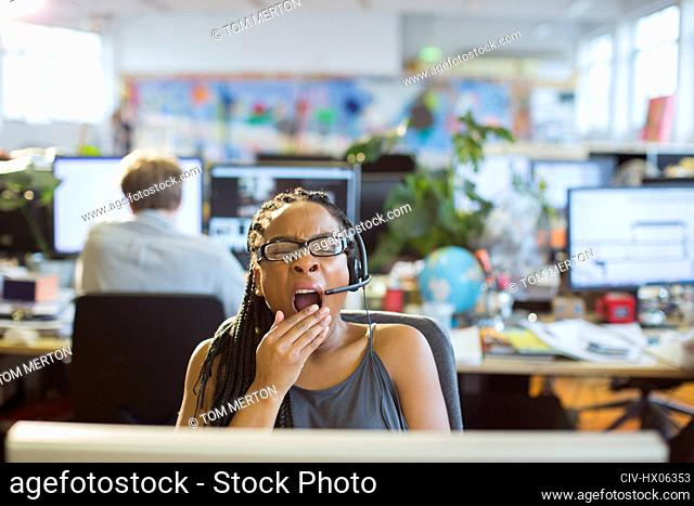 Tired businesswoman with headset yawning at computer in open plan office