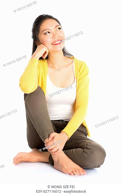 Full length pensive Asian girl sitting on floor smiling and thinking, looking upward, isolated on white background