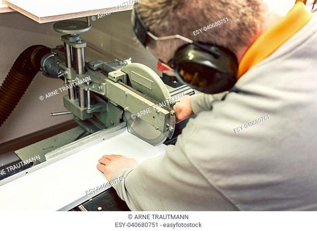 Tinner cutting metal sheets in his workshop with saw, close-up