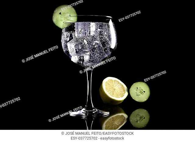 Gin tonic with lemmon and cucumber on black background