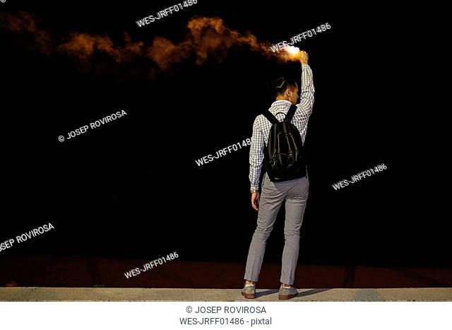 Back view of man with backpack and flame at night