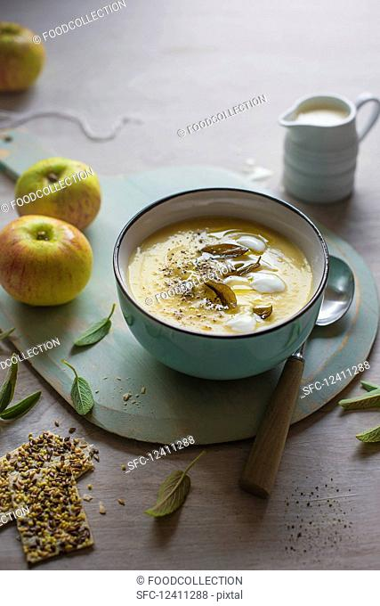 A bowl of celeriac and apple soup with sage and crackers