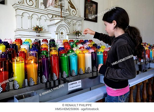 Canada, New Brunswick, the Acadian coast, Caraquet, Sainte Anne du Bocage sanctuary, the Chapel, young girl lightning a candle