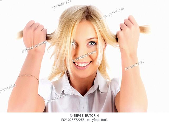 Young beautiful woman smiles with hands in hair over isolated background
