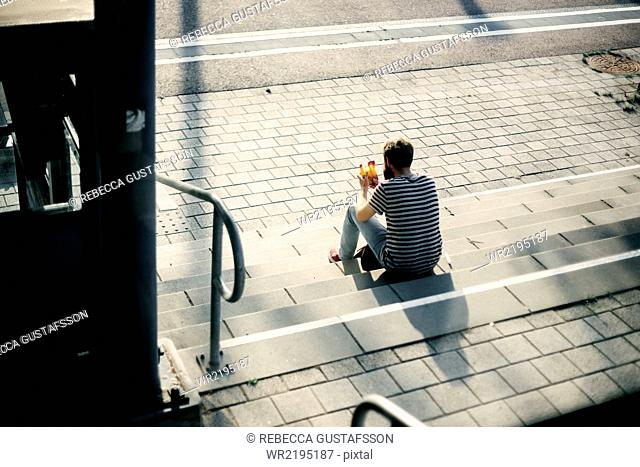 Rear view of man holding food package while sitting on steps