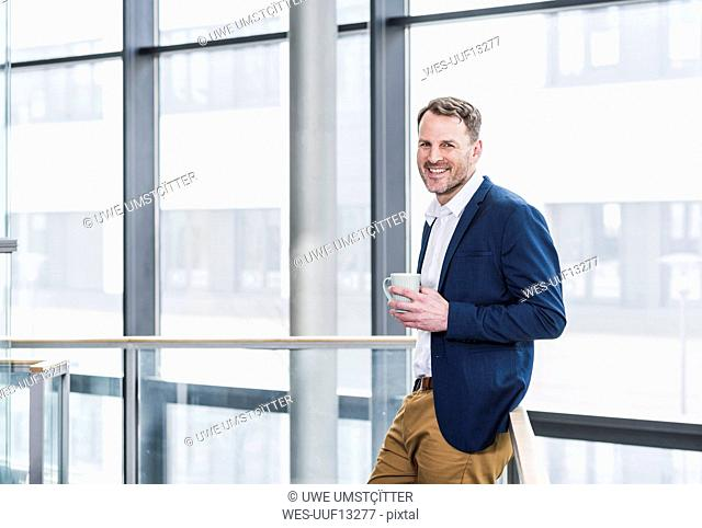 Portrait of smiling businessman having a coffee break