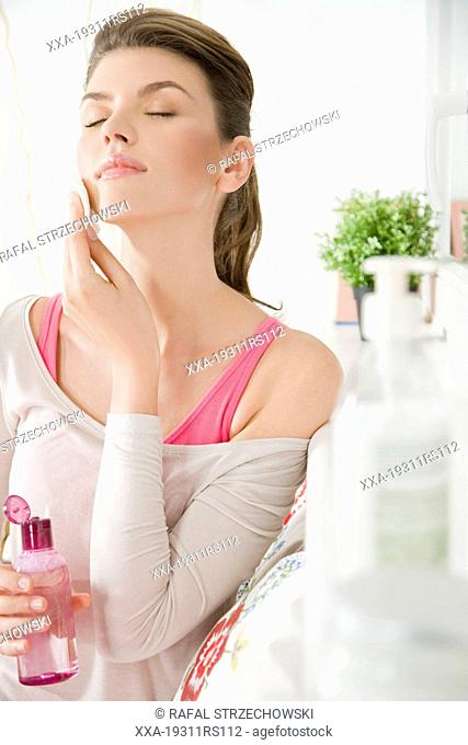 Woman using face lotion