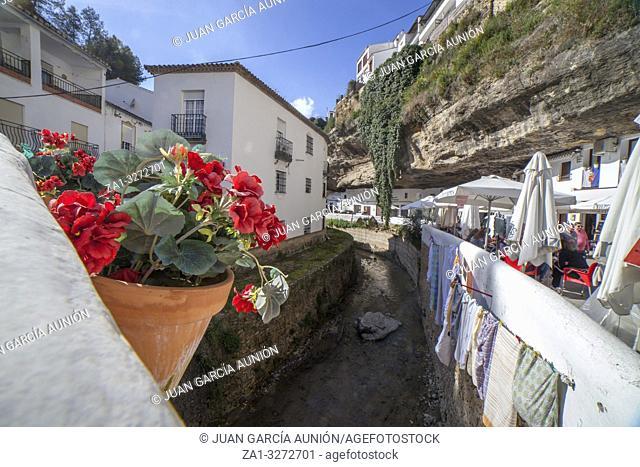 Setenil, Spain - March 4th, 2019: Street with dwellings built into rock overhangs. Setenil de las Bodegas, Cadiz, Spain. View from bridge