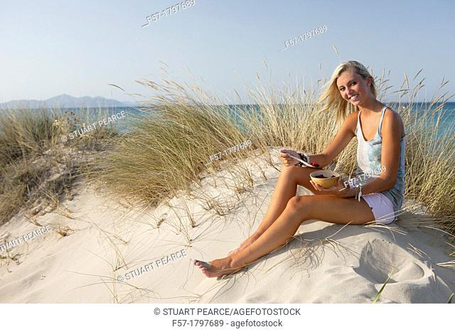 Healthy young woman eating fruit at the beach