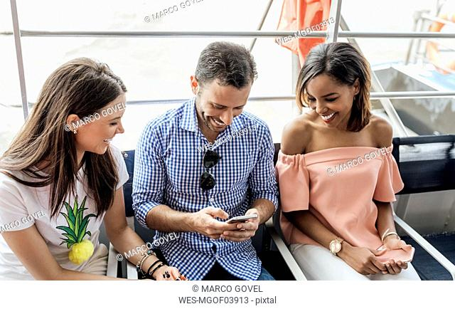 UK, London, happy friends using cell phone while traveling by boat on the River Thames