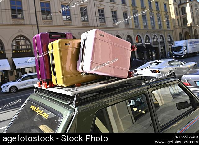 A car, a small car, is parked on the side of the road on Maximilianstrasse. On its roof rack there are suitcases, suitcases