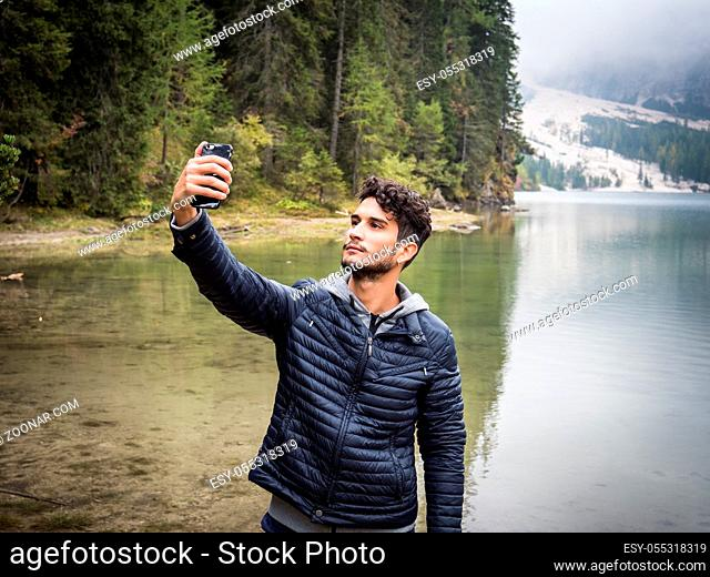 Young handsome man taking selfie with smartphone at lake in forest