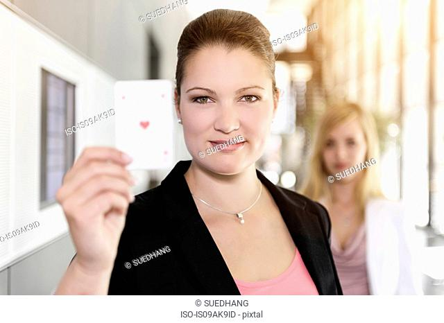 Businesswoman holding up Ace of Hearts card