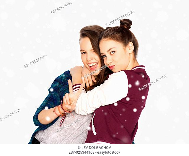 winter, christmas, people, teens and friendship concept - happy smiling pretty teenage girls or friends hugging and showing peace hand sign over gray background...