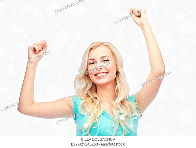 emotions, expressions, winter holidays, success and people concept - happy young woman or teenage girl celebrating victory over snow