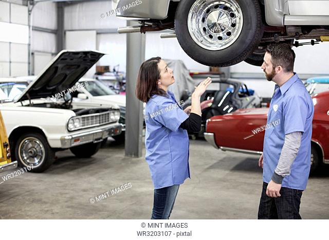 Two Caucasian male and female car mechanics at work on a car in a classic car repair shop